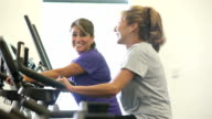 Two mature women talking, working out on exercise bikes video