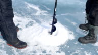 Two men are drilled ice ice screws. video