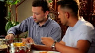 Two men eating a pitta in the indian restaurant video
