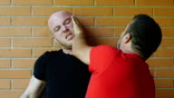 two men fighting against a wall: fight, quarrel. Slowmotion video