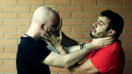 two men fights putting their hands over faces and neck Slowmotion video