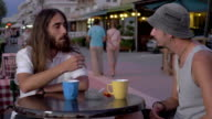 Two men having talk and drinks in street cafe video