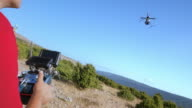 Two men holding controllers and landing drone on sunny hilltop video