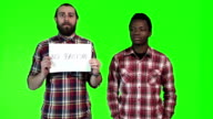 Two men holding up No Racism sign video