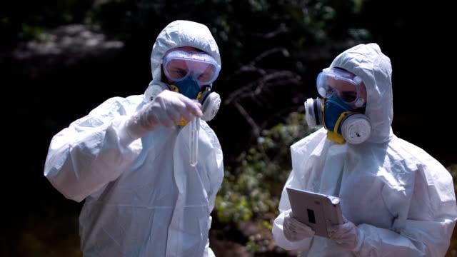 Two men in biohazard suits sampling water video