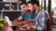 Two Men In Cafe Working On Laptop Together video