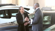 Two men in parking lot talk, embrace and shake hands video