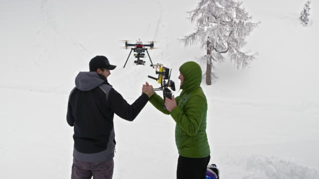 Two men landing a drone in the snow and doing high five video