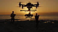Two men landing a drone on beach at sunset video