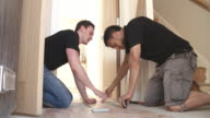 Two men laying laminate wood panel flooring in a house video