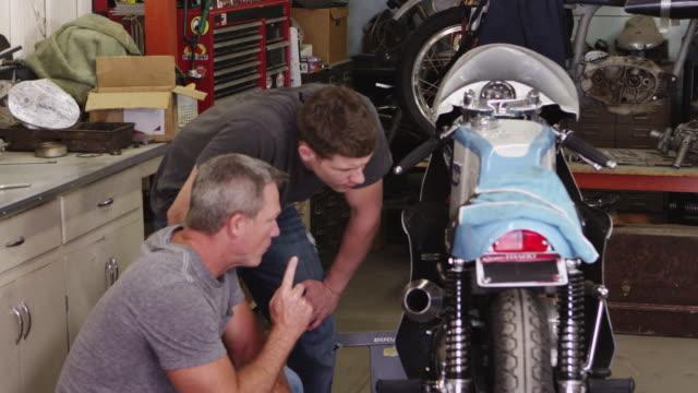 Two men looking over motorcycle video