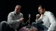 Two men observing a belly dancer while smoking water pipe video