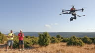 Two men operating a drone on sunny day video