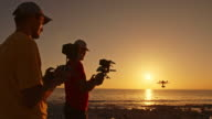 Two men operating drone on the beach in sunset video