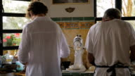 Two men preparing food in a kitchen shot from behind in slow motion video