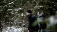 Two men running through the woods. Slow motion video