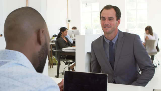 Two men shake hands before an interview in open plan office video
