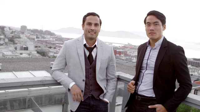 Two men stand on roof while wearing suits and look into the camera video