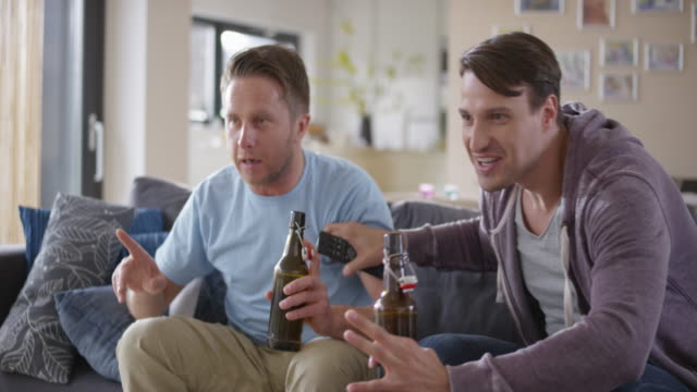 Two men watching a football game and celebrating video