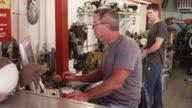 Two men working in a mechanics office video