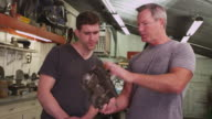 Two men working on motorcycle video