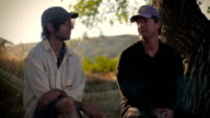 Two middle aged men sit together outside in the wilderness and talk video
