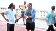 Two middle aged men talking after exercising video