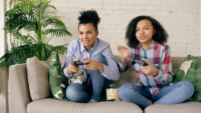 Two mixed race curly girl friends sitting on couch play console computer games with gamepad and have fun at home video