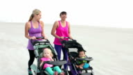Two mothers on beach walking with baby strollers video