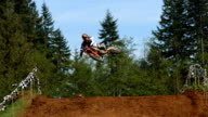 Two motocross racers fly over jump, super slow motion video