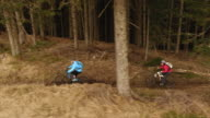 AERIAL Two mountain bikers riding their bikes on a forest trail video
