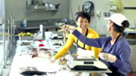 Two multi-ethnic women working in seafood market video