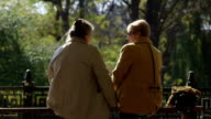 Two older women sitting on a bench talking together enjoying a sunny autumn day video