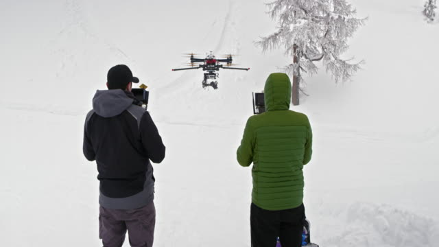 Two operators flying a drone in winter conditions video