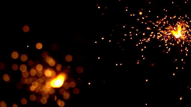 Two orange sparklers against dark background. Super slow motion shallow focus video, 500 fps video