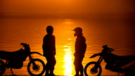 Two other motorcyclists met at beoregu river at sunset. They are happy to see each other and greet. Silhouette against the background of water and sky video