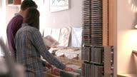 Two people browsing through records at a record shop video