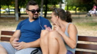 Two people male and female friends sitting on a bench in the park and listening to music played from a smart phone video
