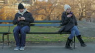 Two people Women and man on a bench smart phones video