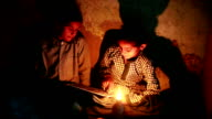 Two poor rural girls studying in lantern at home video