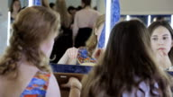 Two pretty girls sit in front of mirror and are apply cosmetics of their faces video