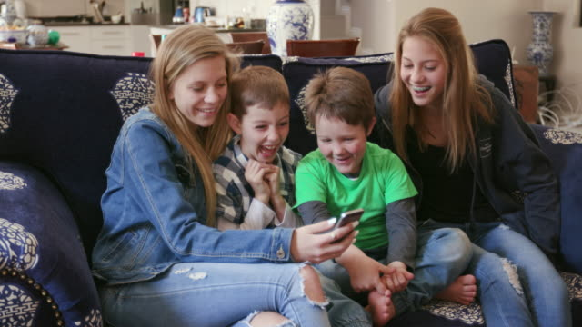 Two pretty young teenage girls and two cute young boys laughing at videos on their phone video