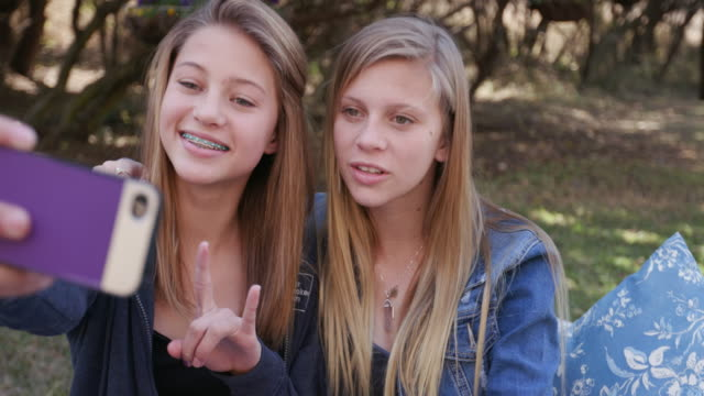 Two pretty young teenage girls taking selfies on their phone and having fun in a park video