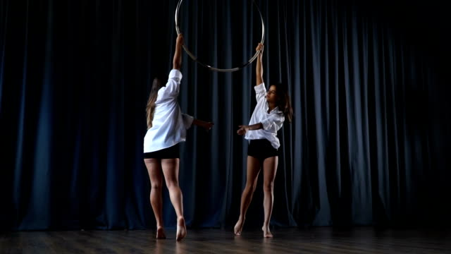 Two professional acrobats performs a trick on the aerial hoop video