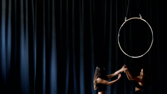 Two professional gymnasts are gesturing hands at the dark curtain background video