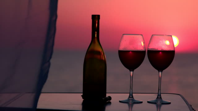 Two red wine glasses at sunset by the sea video