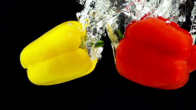 Two Ripe Peppers Falling Through Water. video