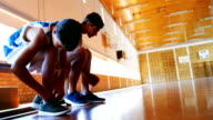 Two schoolboys tying shoe laces in basketball court video
