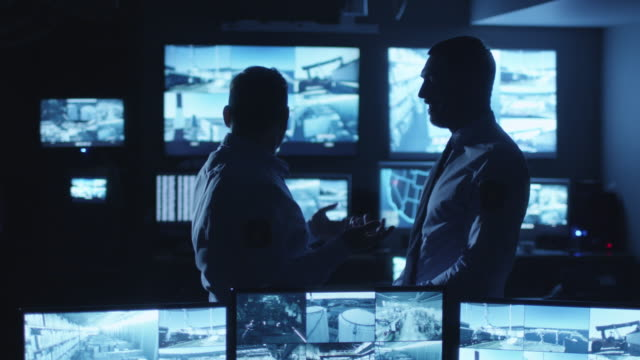 Two security officers are having a conversation in a dark monitoring room filled with display screens. video