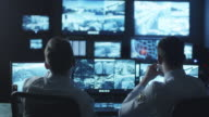 Two security officers are working in a dark monitoring room filled with computer display screens. video